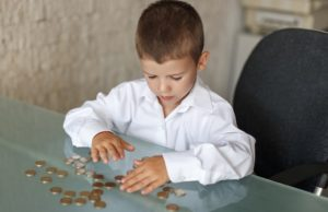 child_with_coins_shutterstock_434800852